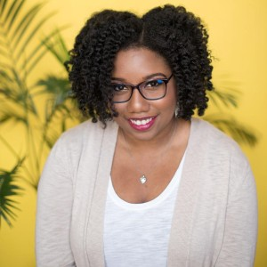 Photo of the author of SLAY, Brittney Morris. She has natural hair, done in a twist out, black glasses, and pinkish red lipstick. She's wearing a white T-shirt with a cream cardigan over it.